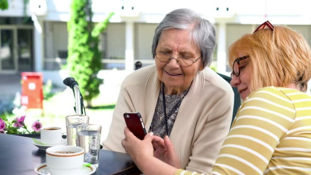 senior woman with daughter sitting in cafe and using a smart phone - active seniors stock videos & royalty-free footage