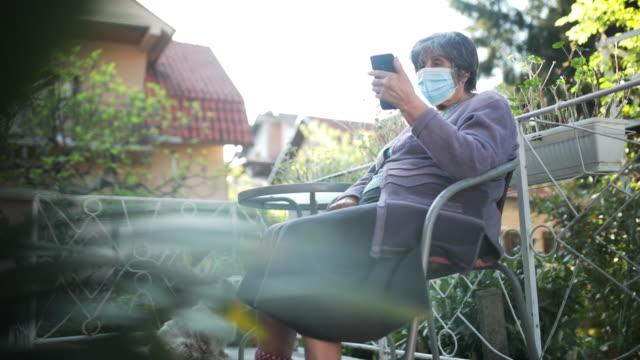 vidéos et rushes de femme aîné avec le masque facial - confinement
