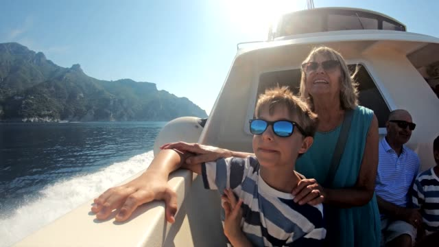 senior woman with grandson travelling by boat near amalfi coast, italy - multi generation family stock videos & royalty-free footage