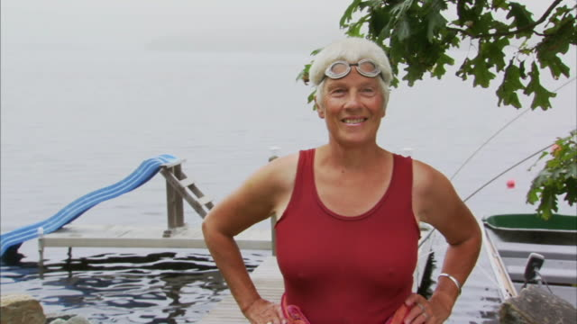 ms portrait senior woman with hands on hip and wearing swim goggles looks at camera smiling / waverly, nova scotia, canada - hand on hip stock videos & royalty-free footage