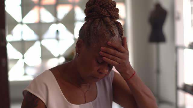 vídeos de stock, filmes e b-roll de idosa com dor de cabeça em casa - cansado