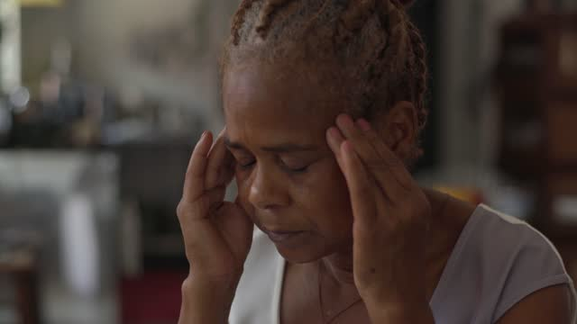 senior woman with headache contemplating at home - cultures stock videos & royalty-free footage