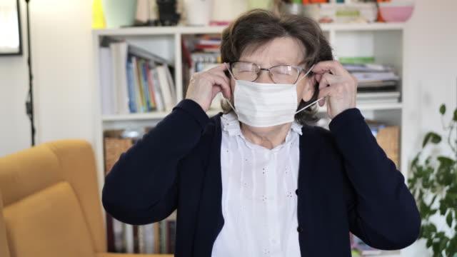 äldre kvinna med hygienisk ansiktsmask hemma - applicera bildbanksvideor och videomaterial från bakom kulisserna