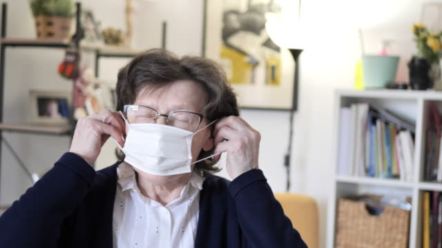 senior woman with hygienic facial mask at home - applying stock videos & royalty-free footage