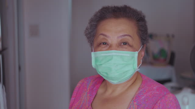 senior woman with hygienic facial mask at home - diabetes prevention stock videos & royalty-free footage