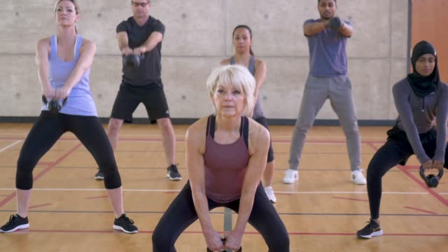 senior woman with kettle bell - sportswear stock videos & royalty-free footage