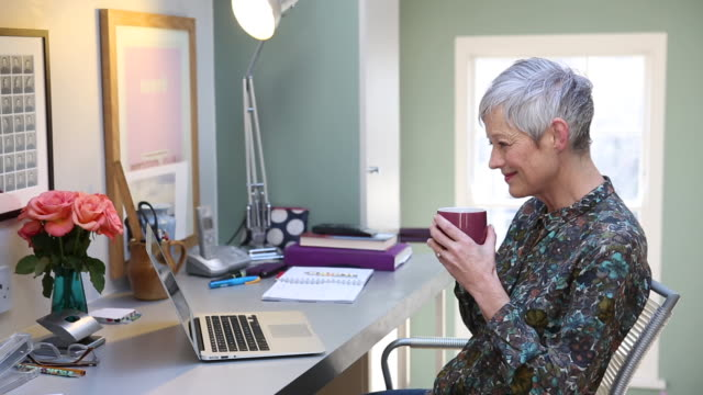 senior woman with laptop at home office. - desk stock videos & royalty-free footage