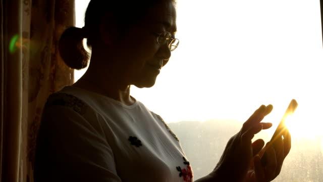 携帯電話を持つシニア女性 - メッセージ点の映像素材/bロール