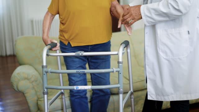 seniorin mit mobilitätswanderer im gespräch mit arzt im pflegeheim - hausbesuch stock-videos und b-roll-filmmaterial