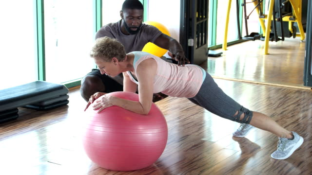 senior woman with personal trainer at gym, planks - instructor stock videos & royalty-free footage