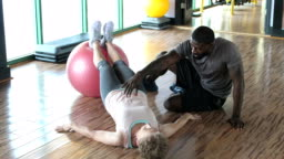 Senior woman with personal trainer at gym, planks