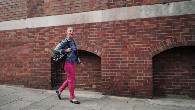 vídeos de stock e filmes b-roll de senior woman with rucksack walking n the city - 60 64 anos