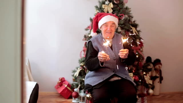 senior woman with santa hat and sparklers on new year's day having fun