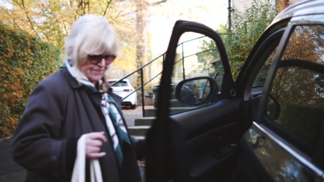senior woman with shopping bag entering car parked at roadside during autumn - 乗り込む点の映像素材/bロール