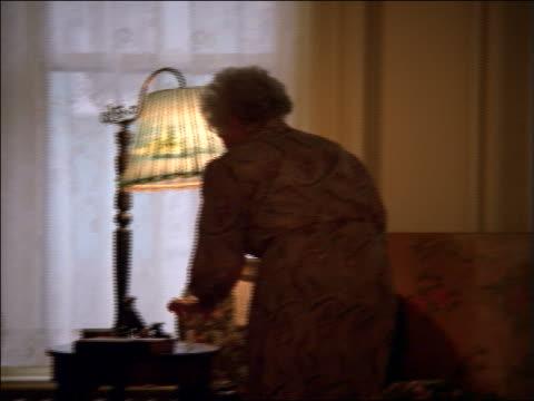 vídeos de stock e filmes b-roll de pan senior woman with teacup walking to armchair, sitting down + picking up book - sentar se