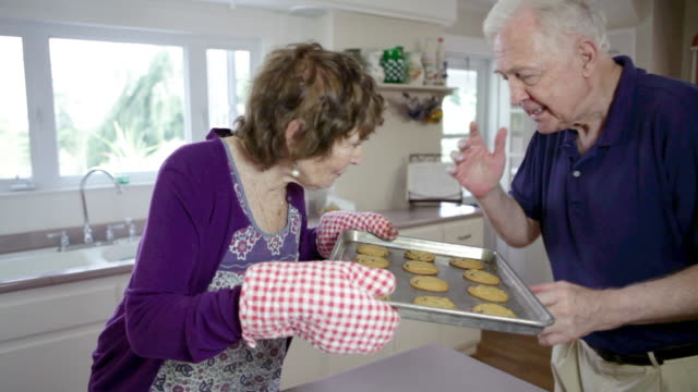senior woman with tray of cookies - oven mitt stock videos and b-roll footage