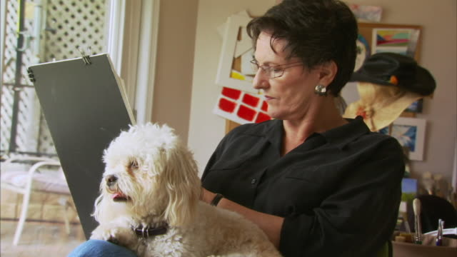 MS Senior woman with white dog on laps drawing, Waverly, Nova Scotia, Canada