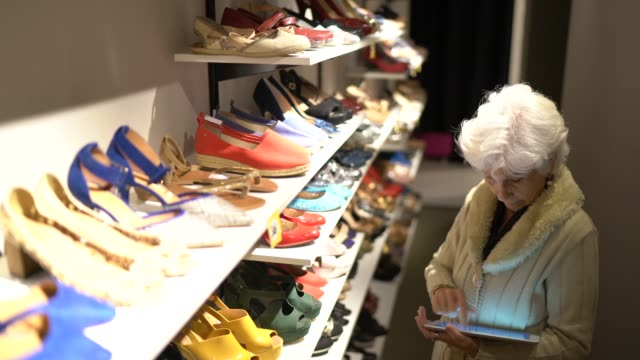 senior woman wlaking in a shoe store with a digital tablet to check store's inventory - clothes shop stock videos & royalty-free footage