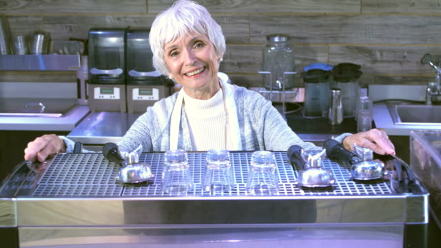 senior woman working behind the counter in a coffee shop - espresso maker stock videos and b-roll footage