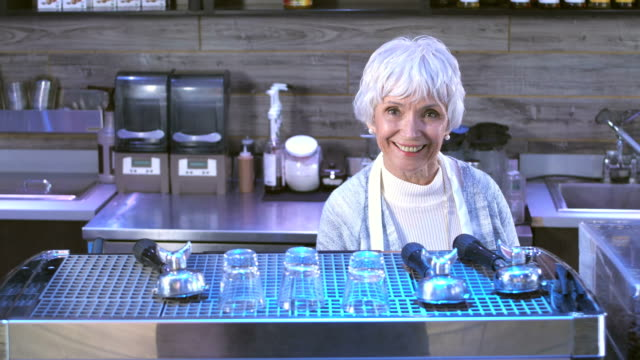 Senior woman working behind the counter in a coffee shop