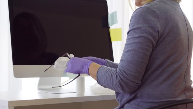 senior woman working from home during pandemic isolation - reading glasses stock videos & royalty-free footage