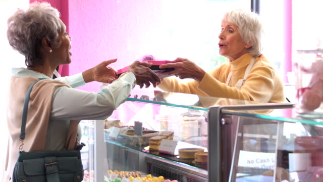 senior woman working in pastry shop helping customer - shop assistant stock videos & royalty-free footage
