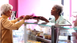Senior woman working in pastry shop helping customer