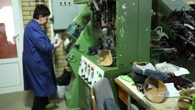 Senior woman working in shoe factory