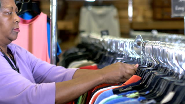 senior woman working in store, hanging clothes on rack - assistant stock videos & royalty-free footage