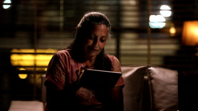 senior woman working on digital tablet at night, delhi, india - sitting stock videos & royalty-free footage