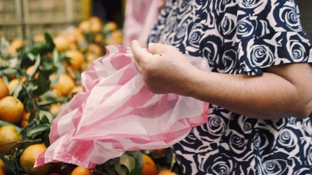 Main de femme Senior choisir orange au supermarché