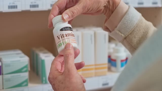 senior woman's hand holding a bottle of d3 vitamins at the drugstore and turning it to check the label - vitamin stock videos & royalty-free footage