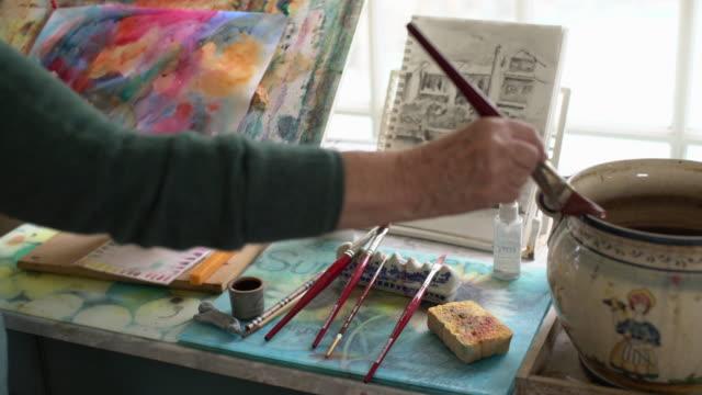 vídeos y material grabado en eventos de stock de cu senior woman's hands painting in her studio - decoración objeto