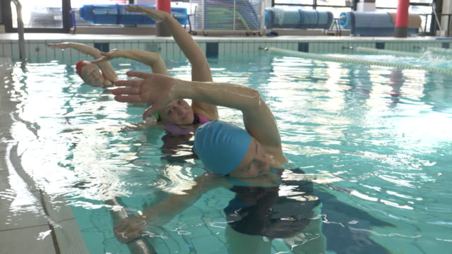 senior women and man taking part in an aqua aerobics class in an indoor swimming pool - aerobics stock videos & royalty-free footage