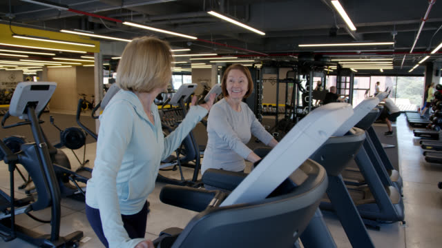 senior women at the gym exercising on treadmill while talking - cross trainer stock videos & royalty-free footage