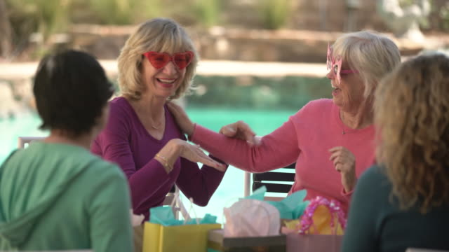 ms senior women chatting and laughing at poolside party - frauen über 40 stock-videos und b-roll-filmmaterial