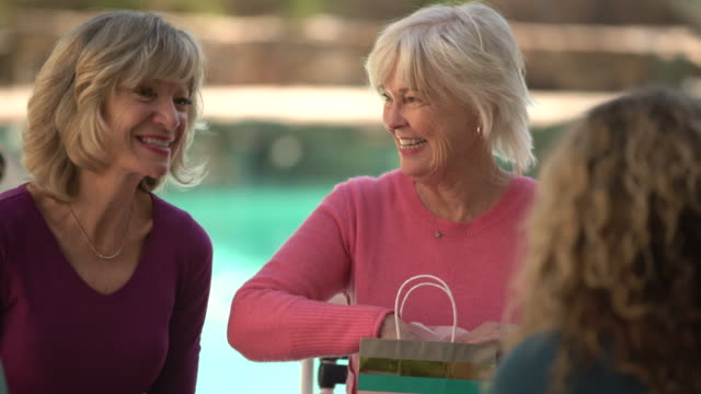 MS Senior women chatting and laughing at poolside party