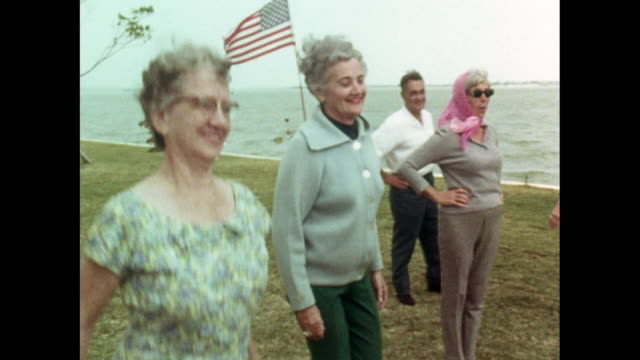 vídeos de stock e filmes b-roll de senior women do group exercise class outside; 1969 - patriotismo