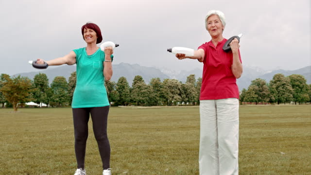 DS Senior women doing hand weight exercises in park