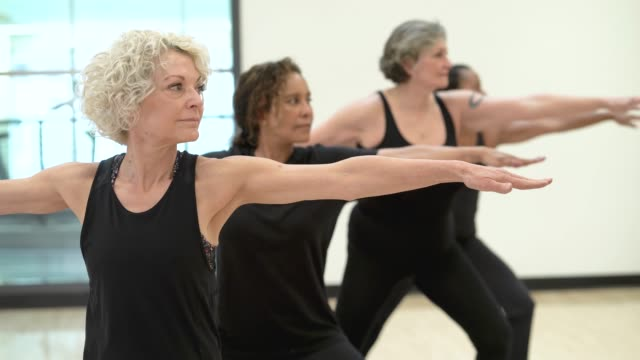 senior women doing yoga - 60 69 years stock videos & royalty-free footage