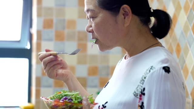 サラダを食べる先輩女性 - 手に持つ点の映像素材/bロール