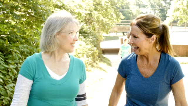 senior women encouraging each other as they exercise and walk in park - racewalking stock videos and b-roll footage