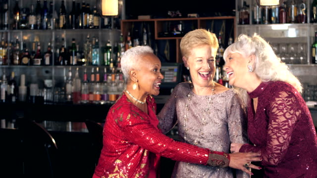 Senior women enjoying night out, talking at bar