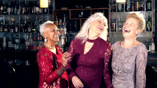 Senior women enjoying night out, talking at bar