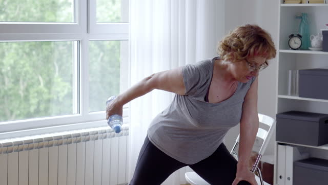 senior women exercise at home - plastic container stock videos & royalty-free footage