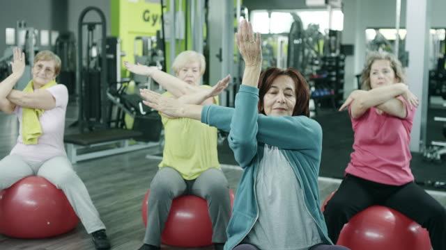 vídeos y material grabado en eventos de stock de senior femenino ejercicio en gimnasio - pilates