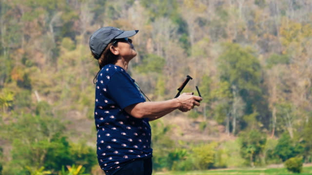 senior women farmer pilot using drone remote controller at rice paddy - drone pilot stock videos and b-roll footage