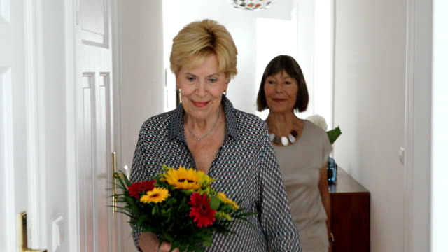 senior women friends in a kitchen with flowers - vase stock videos & royalty-free footage