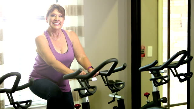 senior women in gym on exercise bike - exercise bike stock videos and b-roll footage