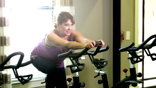 senior women in gym on exercise bike - cross trainer stock videos and b-roll footage